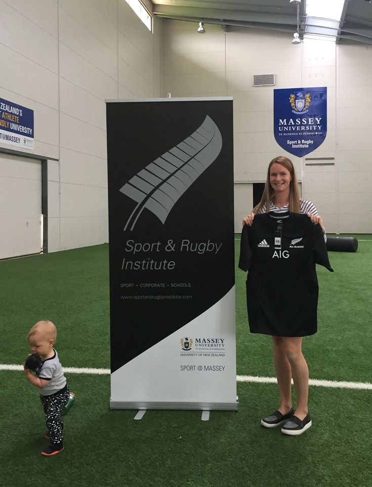 Facebook competition winner, Jess Robinson holding her winning All Blacks jersey, while her toddler explores the SRI